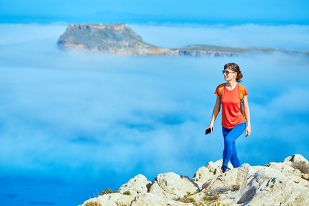 sporty female traveler with backpack standing on the cliff against sea and blue sky with white clouds at early morning, Crete, Greece. woman holding the phone smiling and looking at left side Banque d'images