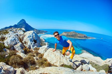 pursue: man runs on a cliff against a blue sea.