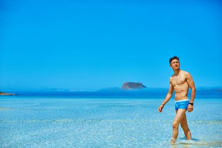 water polo: hombre de pie en el mar en la playa. hombre que lleva en un traje de baño azul