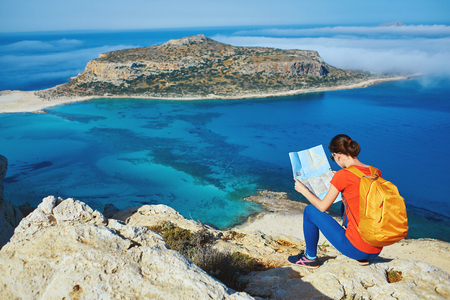 female traveler with backpack and map sitting on the cliff against sea and blue sky at early morning Banque d'images