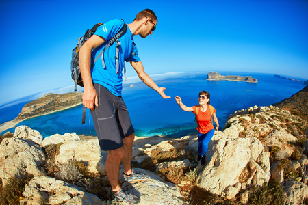 help: couple of travelers with backpack standing on the cliff against sea and blue sky at early morning. Balos beach on background, Crete, Greece. a man helping a woman climb on the rock extends her hand