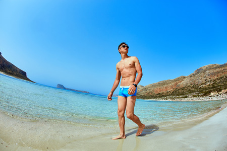 swimming trunks: man standing in the sea on the beach. man wearing in blue swimming trunks Stock Photo