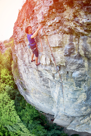 threading: male rock climber. rock climber climbs on a rocky wall. climber threading the rope in quickdraw Stock Photo