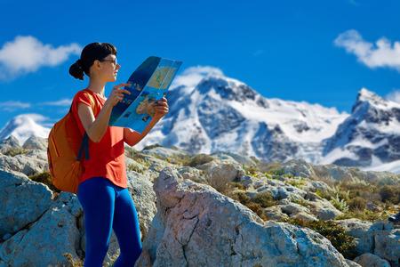 randonneur femme avec sac à dos et plan debout sur la piste contre les grandes montagnes enneigées et le ciel bleu au début de la matinée et à la recherche sur la carte. Banque d'images