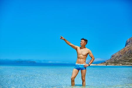 im Meer auf dem Strand Mann. in blauen Badehose und zeigt durch seine rechte Hand auf die rechte Seite trägt Mann
