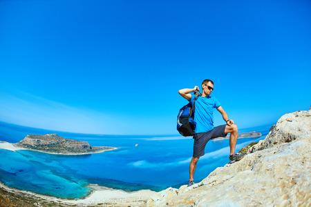voyageur mâle avec sac à dos, debout sur le sentier sur la falaise contre la mer et le ciel bleu au début de la matinée. plage Balos sur fond, Crète, Grèce Banque d'images