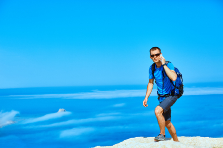 male traveler with backpack standing on the trail on the cliff against sea and blue sky at early morning. Balos beach on background, Crete, Greece. Hiker call by the phone Banque d'images
