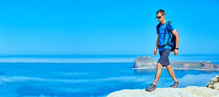 male traveler with backpack standing on the trail on the cliff against sea and blue sky at early morning. Balos beach on background, Crete, Greece Banque d'images