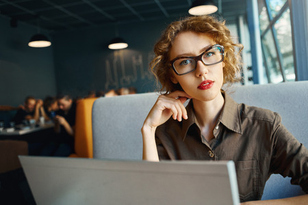 appraising: handsome woman sitting in a cafe near the open laptop at a table made of wood . in the background a bright window with bright daylight. woman looking serious appraising glance