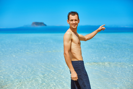 adult cruise: man standing in the sea on the beach. Smiling man looking at camera and shows to the side by his hand