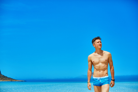 bared: strong athletic man with bared torso standing on the beach along the sea front Stock Photo