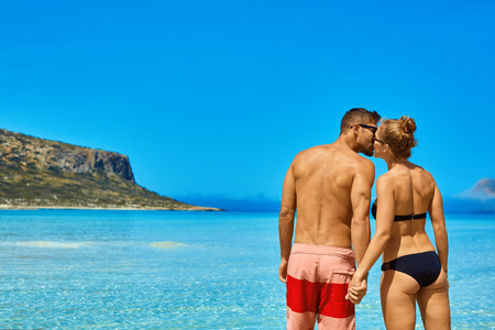 adult cruise: couple standing in the sea near the boat. Stock Photo