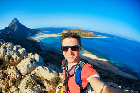 homme voyageur avec sac à dos, debout sur la falaise contre la mer et le ciel bleu au début de la matinée. plage Balos sur fond, Crète, Grèce. homme prenant une selfie