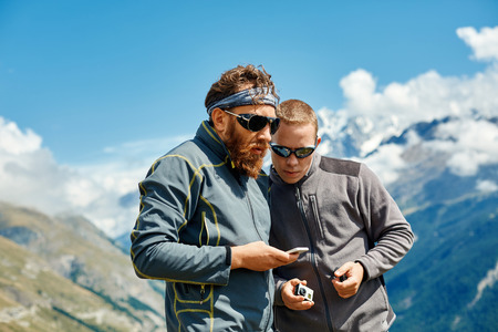 hikers at the top of a pass with smartphone and action camera enjoy sunny day in Alps. Switzerland, Trek near Matterhorn mount. try to configure the device to work together