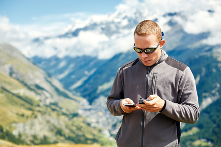 configure: hiker at the top of a pass with smartphone and action camera enjoy sunny day in Alps. Switzerland, Trek near Matterhorn mount. try to configure the device to work together