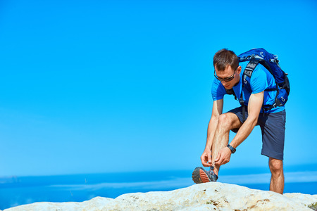 lace up: man runs on a rock against a blue sea. man leaned lace up sneakers Stock Photo