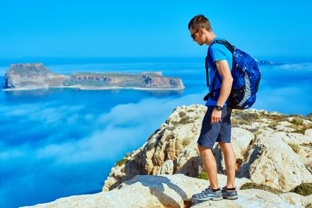 voyageur mâle avec sac à dos, debout sur le sentier sur la falaise contre la mer et le ciel bleu au début de la matinée. plage Balos sur fond, Crète, Grèce