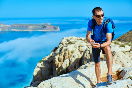 male traveler with backpack standing on the trail on the cliff against sea and blue sky at early morning. Balos beach on background, Crete, Greece. man holding a phone or gps navigator and look choosing the direction of motion
