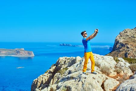 homme voyageur debout sur la falaise contre la mer et le ciel bleu au début de la matinée. plage Balos sur fond, Crète, Greecee. l'homme de prendre une photo sur un smartphone Banque d'images