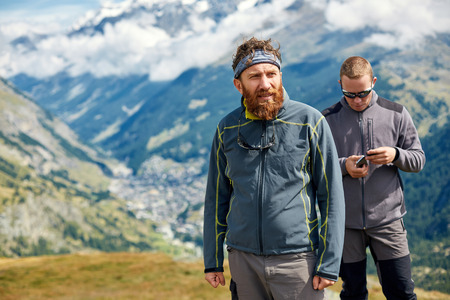 configure: hikers at the top of a pass with smartphone and action camera enjoy sunny day in Alps. Switzerland, Trek near Matterhorn mount. try to configure the device to work together