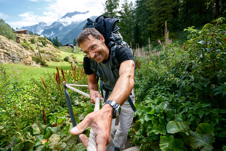 hiker in the Apls mountains. Trek near Matterhorn mount. a man with a happy face on a rope climbs Stock Photo