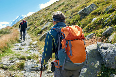 hikers with backpacks on the trail in the Apls mountains. Trek near Matterhorn mount Stock Photo