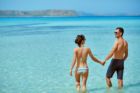 young happy couple in love walking on the beach at the sunny day. Balos beach, Crete, Greece. newlyweds in a honeymoon on the sea and islands Stock Photo