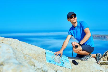voyageur mâle avec sac à dos et plan debout sur la falaise contre la mer et le ciel bleu au début de la matinée