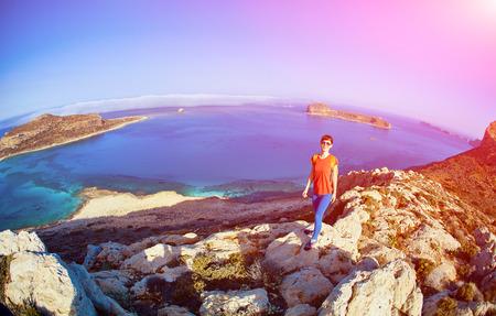 voyageuse sportive avec sac à dos, debout sur la falaise contre la mer et le ciel bleu avec des nuages ??blancs au début de la matinée, Crète, Grèce. Banque d'images