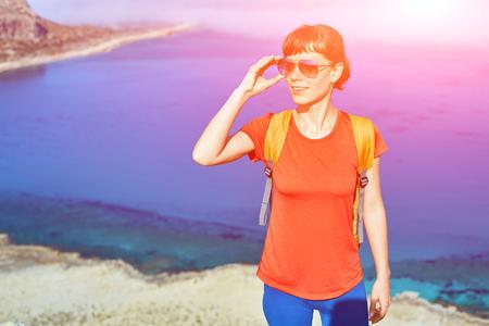 femme voyageant avec sac à dos debout sur la piste contre la mer et le ciel bleu au début de la matinée