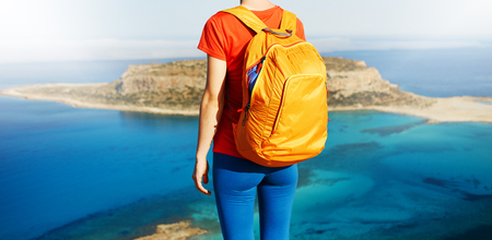 female traveler with backpack standing on the trail against sea and blue sky at early morning. Balos beach on background, Crete, Greece