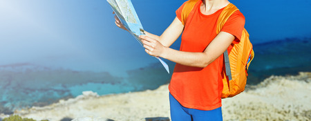 female traveler with backpack and map standing on the trail against sea and blue sky at early morning Banque d'images