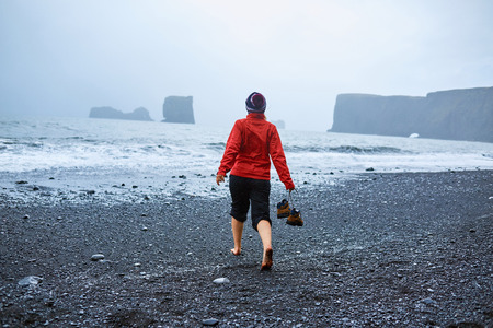 adult footprint: woman walking along the beach in a storm. black sand beaches on the Atlantic coast in Iceland