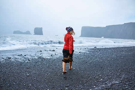 woman walking along the beach in a storm. black sand beaches on the Atlantic coast in Iceland