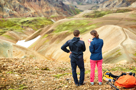 couple hikers National Park Landmannalaugar, Iceland. woman resting and eating figs