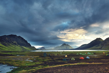 Travel to Iceland. Beautiful Icelandic landscape with mountains, sky and clouds. Trekking in national park Landmannalaugar. Rainy Evening in Camping near Alftavatn lake. Tents and hikers in the camping.