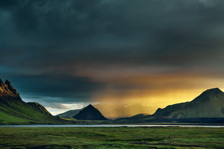 Travel to Iceland. Beautiful sunset in camping near Alftavatn lake. Icelandic landscape with mountains, sky and clouds. Trekking in national park Landmannalaugar. Rainy Evening with big rainbow. Stock Photo