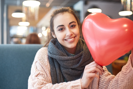Happy smiling woman with balloon in the form of heart in a cafe. Couple in love on a date. Love story and Valentines Day concept