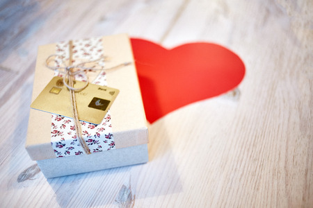 gift box with credit card and paper heart on the wooden table. Valentines day concept