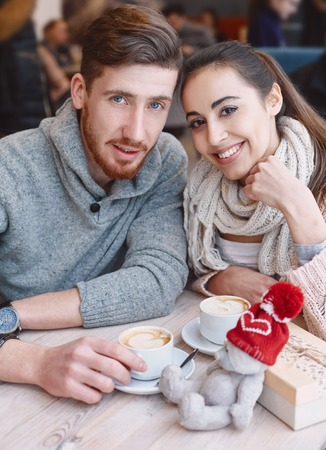 beguin: Two people, man and woman in cafe communicate, laughing and enjoying the time spending with each other. Couple in love on a date. A woman receives a gift from a man. Presented with a teddy bear in a red cap. Love story and Valentines Day concept
