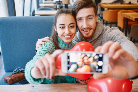 beguin: man and woman doing selfie with balloon in the form of heart in a cafe. Two people communicate, laughing and enjoying the time spending with each other. Couple in love on a date. Love story and Valentines Day concept