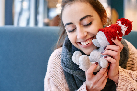 beguin: Couple in love on a date. A woman receives a gift from a man. Presented with a teddy bear in a red cap. Love story and Valentines Day concept