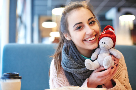 Couple in love on a date. A woman receives a gift from a man. Presented with a teddy bear in a red cap. Love story and Valentines Day concept