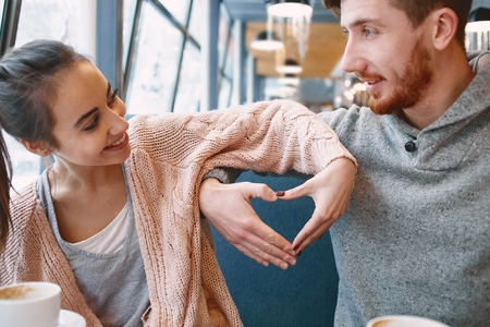 man and woman smiling with hands depict the heart. Two people, man and woman in cafe communicate, laughing and enjoying the time spending with each other. Couple in love on a date. Love story and Valentines Day concept Stock Photo