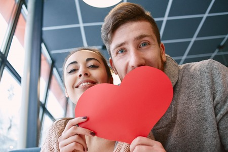 beguin: man and woman smiling and holding a large paper heart. Two people, man and woman in cafe communicate, laughing and enjoying the time spending with each other. Couple in love on a date. Love story and Valentines Day concept