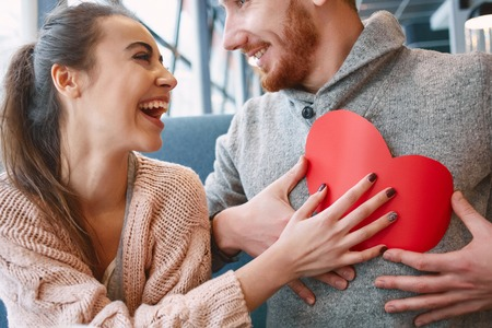 man and woman smiling and holding a large paper heart. Two people, man and woman in cafe communicate, laughing and enjoying the time spending with each other. Couple in love on a date. Love story and Valentines Day concept Imagens - 70861901