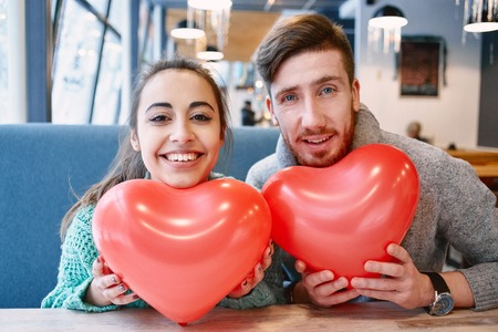beguin: man and woman with balloon in the form of heart in a cafe. Two people communicate, laughing and enjoying the time spending with each other. Couple in love on a date. Love story and Valentines Day concept Stock Photo