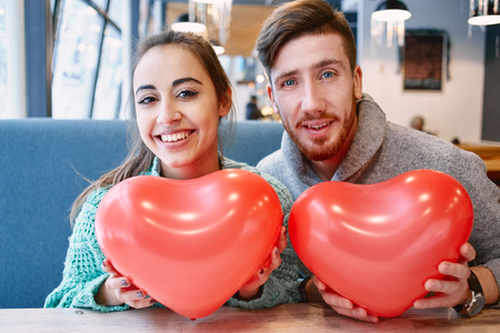 amorousness: man and woman with balloon in the form of heart in a cafe. Two people communicate, laughing and enjoying the time spending with each other. Couple in love on a date. Love story and Valentines Day concept Stock Photo