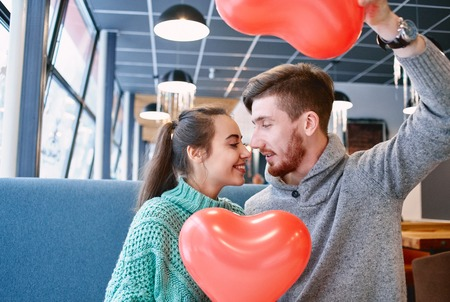 man and woman with balloon in the form of heart in a cafe. Two people communicate, laughing and enjoying the time spending with each other. Couple in love on a date. Love story and Valentines Day concept Imagens