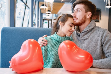 man and woman with balloon in the form of heart in a cafe. Two people communicate, laughing and enjoying the time spending with each other. Couple in love on a date. Love story and Valentines Day concept Stock Photo